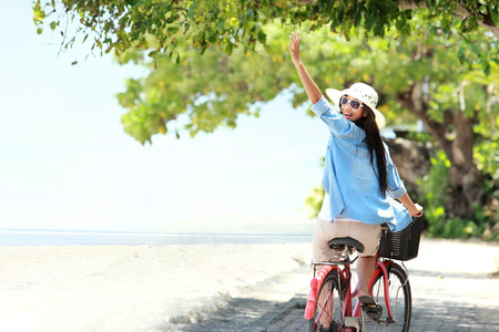 carefree woman having fun riding bicycle and raised her arm at the beach photo