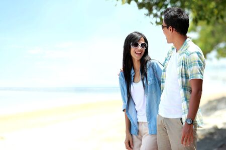 Portrait of happy couple walking by the beach photo