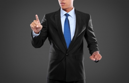 Business Man pushing on a touch screen interface  against black background Stock Photo - 24980058