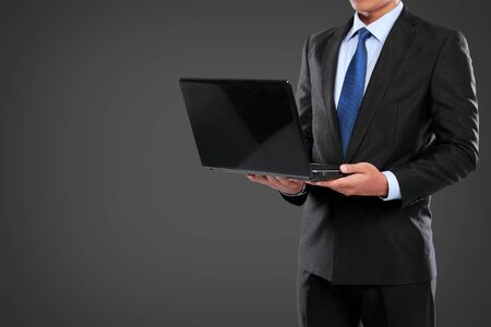 Businessman working on a laptop computer against black background photo