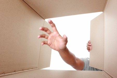 reaching hand: hand trying to grab something inside box