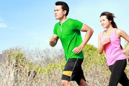 Deportivo joven pareja asiática que se ejecuta fuera juntos
