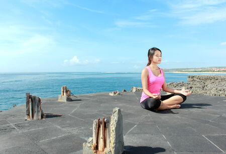 portrait of asian girl on the beach doing meditation photo