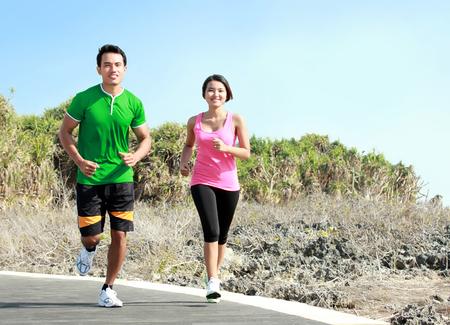 salud y deporte: Deportivo joven pareja asi�tica que se ejecuta fuera juntos en pista de jogging Foto de archivo