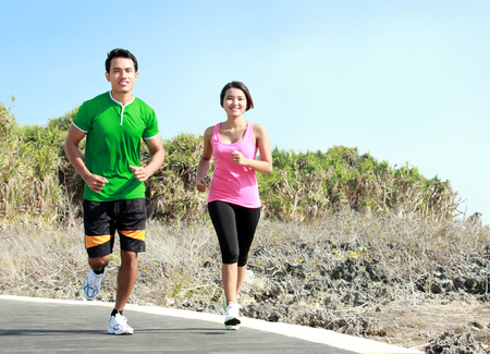 Sporty asian young couple running outside together on jogging track