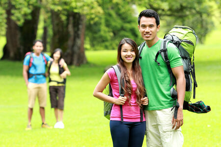 camping concept. Portrait of young man and woman with backpack camping together in the park photo