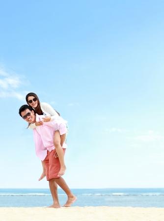 Człowiek nosić dziewczynę na plecach wspólnej zabawy na plaży Zdjęcie Seryjne