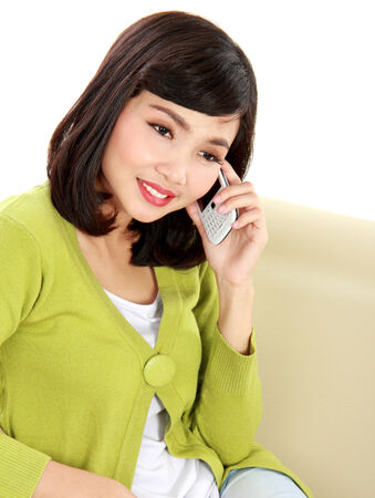 Smiling woman calling someone using cellphone on couch photo