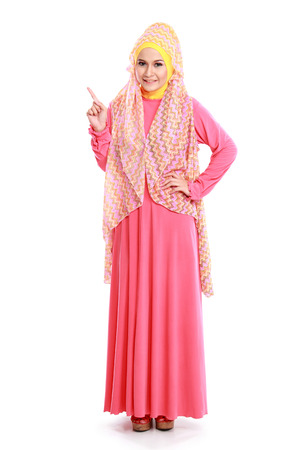 beautiful woman wearing pink muslim dress pointing isolated on white background photo