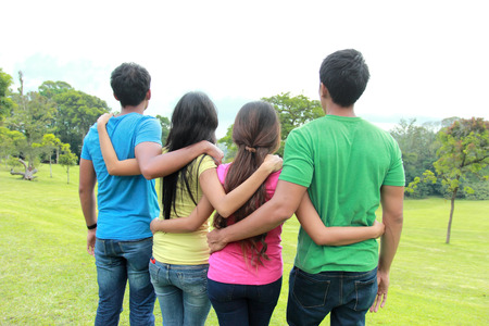 portrait of group of four people holding each other. shoot from behind 版權商用圖片 - 25351831