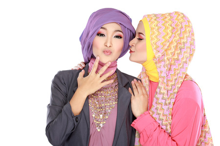 moslem: Portrait of two beautiful muslim woman having fun together isolated over white background