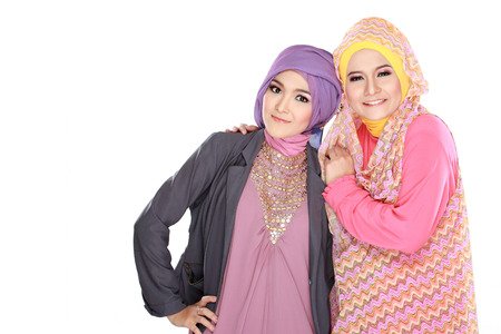 Portrait of two beautiful muslim woman having fun together isolated over white background photo