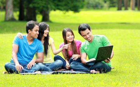 educacion universitaria: Grupo de estudiante joven que usa el ordenador port�til juntos en el parque Foto de archivo