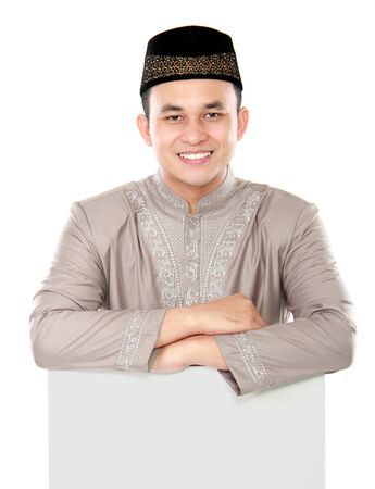 smiling asian muslim man presenting copy space isolated over white background photo