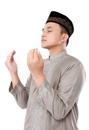 muslim man doing prayer isolated over white background photo