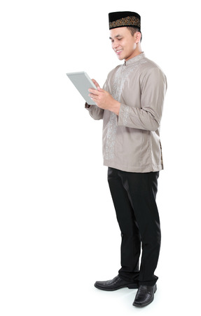portrait of modern muslim man holding tablet pc isolated over white background photo