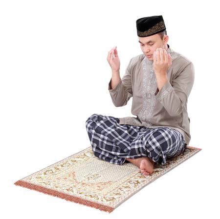 El hombre musulmán haciendo oración aislada sobre fondo blanco Foto de archivo