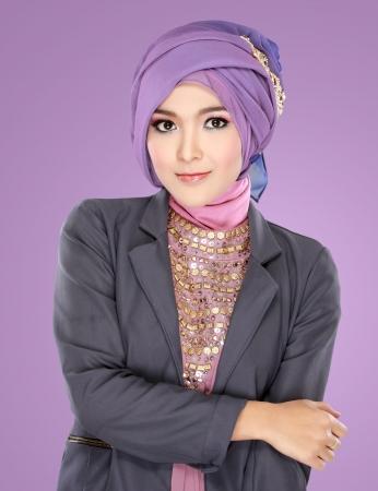 glamour model: Fashion portrait of young beautiful muslim woman with purple costume wearing hijab