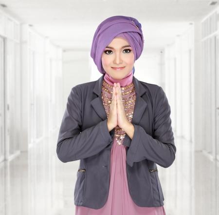 mooie gastvrije meisje dragen hijab lachend op een witte achtergrond Stockfoto