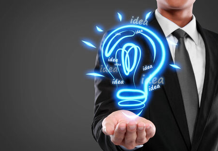 Business man with idea light bulb on virtual background photo