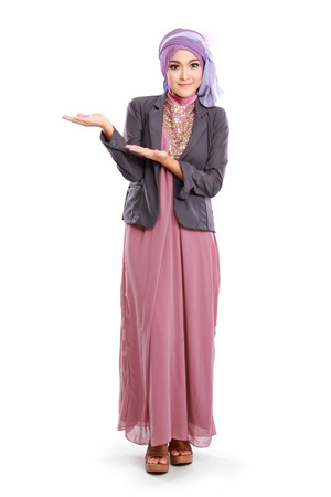hijab: beautiful girl wearing pink muslim dress showing copyspace isolated on white background