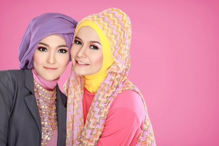 Portrait of two beautiful muslim woman having fun together photo