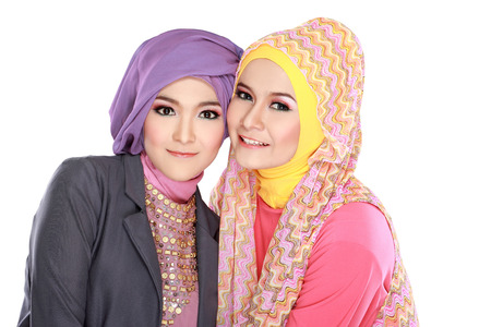 Portrait of two beautiful muslim woman having fun together isolated over white background