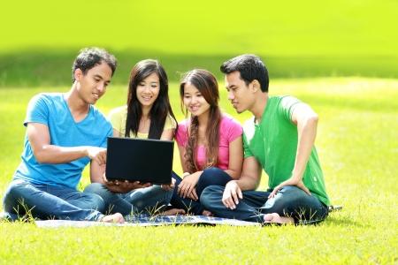 studie: Skupina mladých studentů pomocí notebooku společně v parku
