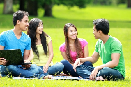 Group of young student using laptop together in the park photo