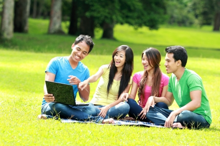asian youth: Group of young student using laptop together in the park Stock Photo