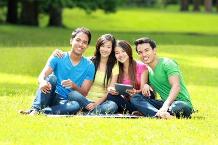 Group of young student using tablet pc together in the park photo