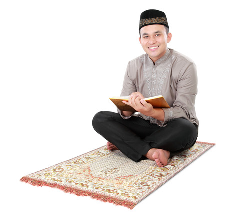 muslim man holding and reading quran isolated over white background photo