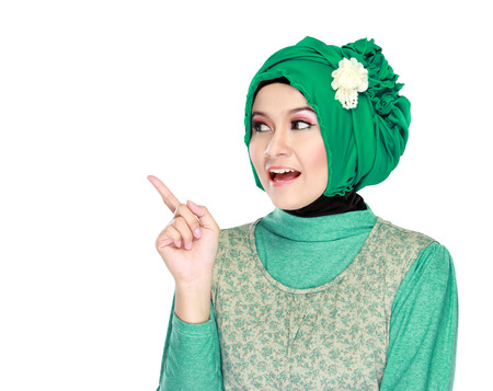 Portrait of beautiful young moslem woman pointing at something isolated on white background