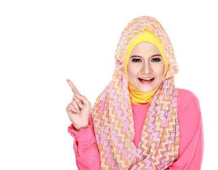 Portrait of beautiful young moslem woman pointing at something isolated on white background photo