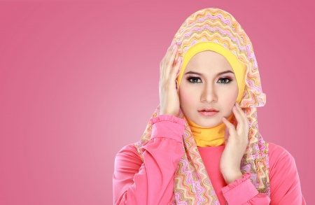 Fashion portrait of young beautiful asian muslim woman with pink costume wearing hijab photo