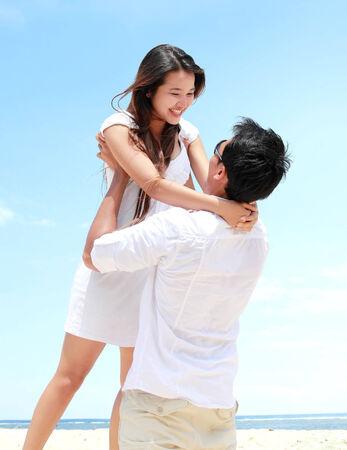 An attractive happy couple having fun on the beach photo