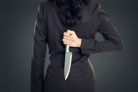 ビジネスの女性ナイフの背後にある彼に戻る所蔵します。概念図 写真素材