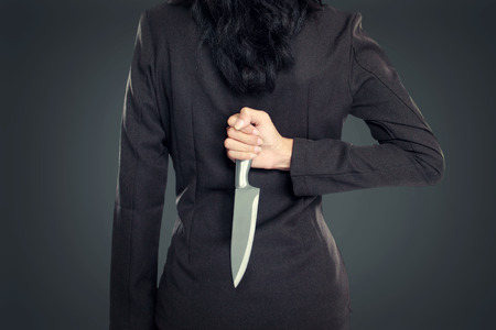 cuchillo: Mujer de negocios con cuchillo en la espalda. imagen conceptual Foto de archivo