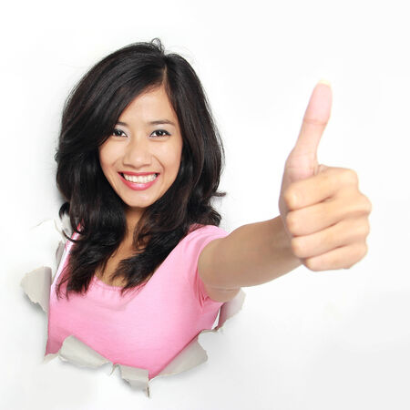 coming out: Young woman coming out of a hole tearing on the white paper showing thumb up Stock Photo