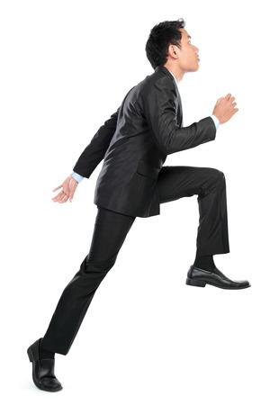 escalando: Hombre de negocios posando para la foto conceptual de subir. aislado en fondo blanco Foto de archivo