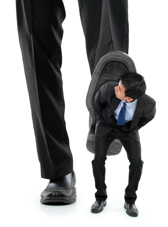 Little business man being crushed by the feet of a giant business man photo