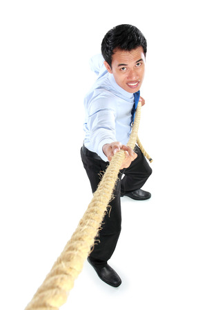 Business competition. Young businessman pulling a rope while standing isolated on white background photo