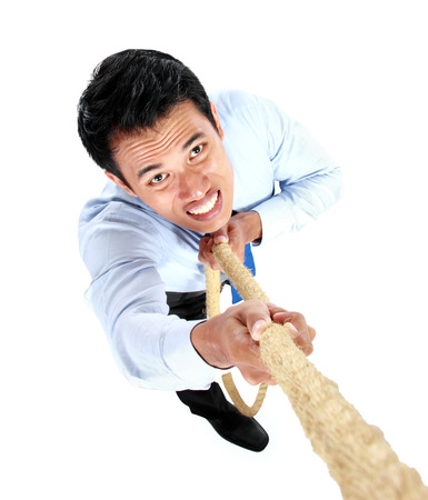 Young businessman climbing up by using a rope isolated on white background Stock Photo