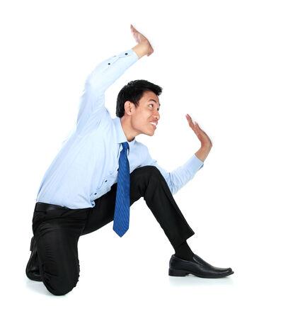 upward struggle: Portrait of businessman posing for conceptual photo. holding something