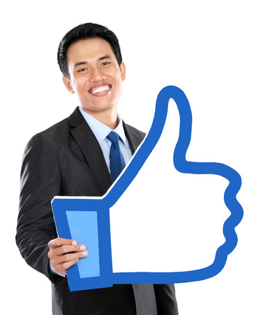 Portrait of businessman holding like or thumb up sign over white background Stock Photo - 25934979