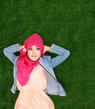 Young muslim girl wearing hijab lying on grass looking up to copyspace