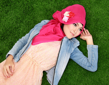 Young muslim girl wearing hijab lying on grass photo