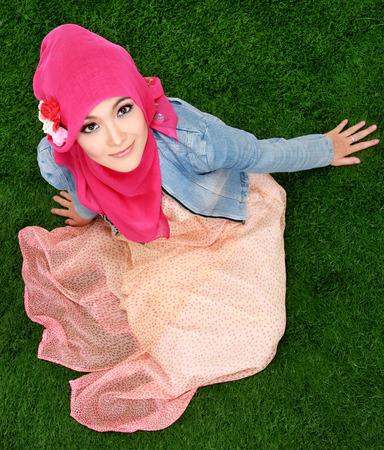Young muslim girl wearing hijab sitting on grass photo