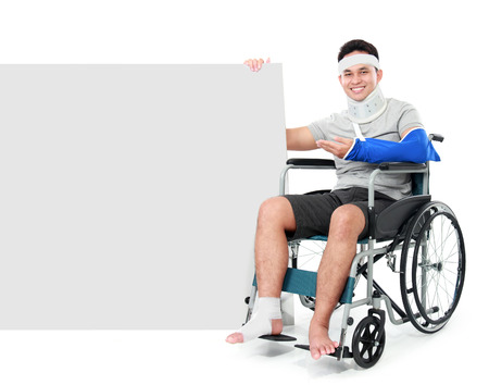 broken chair: male with broken leg sitting on the wheel chair and presenting to blank board isolated on white background