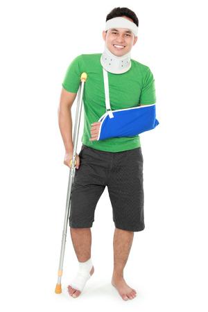 pierna rota: Retrato de cuerpo entero de un hombre que sonríe con el brazo roto y pie con muletas aislados en fondo blanco